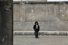 A boy stands near a wall of his school riddled with holes, due to what activists said was an air strike carried out by the Russian air force in Aleppo countryside, January 12, 2016. REUTERS/Khalil Ashawi