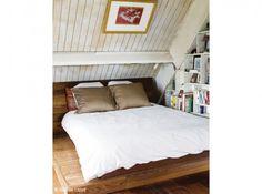 Dans cette chambre à coucher, les pans de murs ont été mansardés de lambris blanc afin d'attirer la luminosité souvent très faible sous les combles.