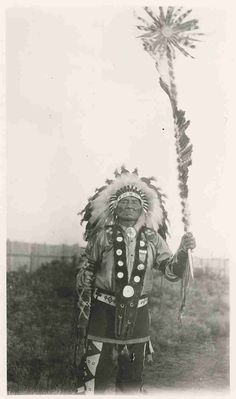 Three-quarters length portrait of Flying Buffalo of the Dakota (Sioux), taken in Prince Albert, Saskatchewan. He is wearing a feathered headdress a.