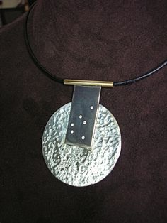 16c0ff5896bd A clean and casual necklace featuring hammered and oxidized Sterling Silver  suspended from a 14K yellow