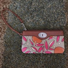 Fossil wristlet Brown wristlet with pink and orange pattern. Excellent condition. The only flaw is there is a little part where the pink on the back looks like it was bleeding through a little but you really can't notice it much :) Fossil Bags Clutches & Wristlets