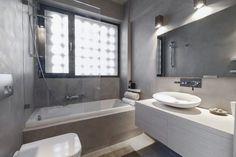 salle de bains avec baignoire, douche, paroi et toilettes, peinte en gris perle