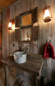 Rustic Bathroom. A galvanized pail is brought to life as a sink in this rustic barn board bathroom.