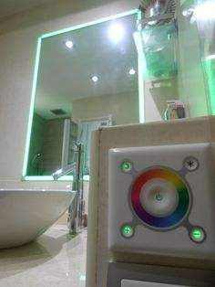 Iluminación de espejo con tiras de led RGB gestionadas por un controlador empotrable táctil. Permite crear un entorno de cromoterapia en el baño.