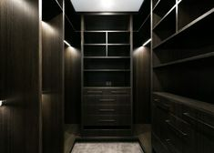 The dark stained timber walk-in closet hosts an array of storage options in various configurations. Inner lighting and minimalist hardware complete the bespoke design. Walk In Robe Designs, Walk In Closet Design, Bedroom Closet Design, Closet Designs, Closet Renovation, Closet Remodel, Apartment Renovation, Bed In Closet, Dressing Room Closet