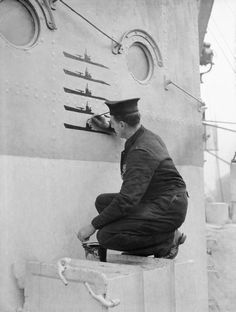 Ordinary Seaman P S Buckingham, keeping a record of U-boat kills on the side of the wheelhouse on board HMS HESPERUS, docked at Liverpool, 6 December 1943.