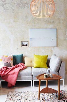 Sofá de tela en azul serenity con manta de color rosa intenso, cojines de colores amarillo, verde, amarillo pálido y un cojín con un zorro pintado. Pared amarillos muy pálido con un tratamiento de desgaste. Lámpara de colgar muy grande en cobre.