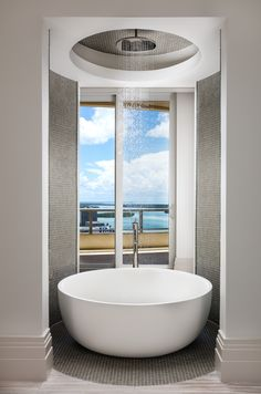 Penthouse round bathtub with rain head shower and glass tile walls, waterview