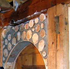 "The arched door was hand built with recycled lumber and the cordwood was infiled around a temporary ""bent"" board."