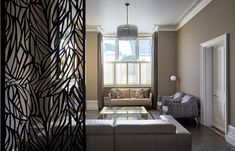 Farrow and Ball dark toned painted walls. Original features in architrave for this Edwardian front room. The lattice work design in the screen perfectly divides the space.