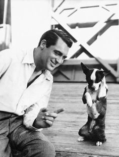 Cary with Squeezit the dog, between takes for When You're In Love, 1937