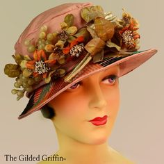 This summer cloche was created with silk dyed to that blushing sunset pink. It is dated to circa 1926 due to the shallow brim and overall silhouette   It is covered with a plethora handmade flowers, foliage and paper thin, blown glass 'wild grapes'. The brim is entirely hand embroidered in geometric lines stitched with multi-plied wool and silk yarn. The silk against fuzzy wool adds subtle iridescence as well as textural interest