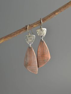 Mixed Metal Earrings  Roll print textured copper triangles are suspended below hammered silver triangles. Fun geometric earrings to wear with your favorite mixed metal jewelry! Metal has a brushed patina finish to highlight the texture.  Hypo allergenic titanium earwires. Earrings measure approximately 2 inches long including the length of the earwires.