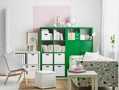 Olohuone, jonka vihreät ja valkoiset hyllyt ovat täynnä kirjoja ja laatikoita. Huoneessa myös pinkki-vihreä sohva ja valkoinen pikkupöytä.