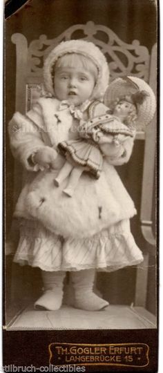 Vintage Photo of a child with her doll. She is wearing a white ermine coat. c1900. The doll is beautifully dressed with a fancy hat.