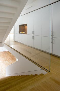 FLOORING STAIRCASE Custom wood and glass staircase next to a wall of cabinets