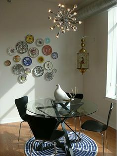 "How-To: Decorate on the Cheap With Pretty Plates: While some may call plate decorating ""grandma style,"" this home proves that modern and classic elements can blend perfectly in a space. The classic look of hung plates looks great with the modern chandelier and chairs.   Source"