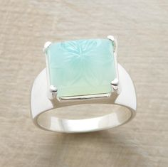 "A bounteous blossom is hand carved into our chunk of sea green chalcedony. Sterling silver band and bezel. Whole sized 6 to 10. Tapers 3/8"" to 1/8""W."