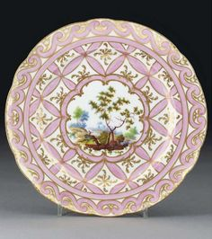 A Nantgarw (London-decorated) plate  CIRCA 1820, IMPRESSED MARK  Painted with a figure in a wooded river landscape, within a lobed cartouche edged in pink with gilt C-scrolls, the plain border reserved with pink geometric petal design below S-scroll border   9½ in. (24 cm.) wide