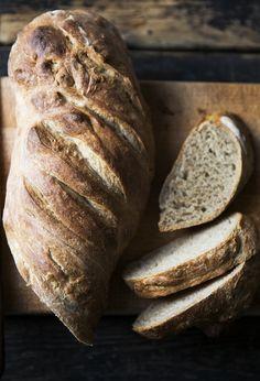 Friskbagt brød med en sprød skorpe og et par friskskårede skiver ved siden af.