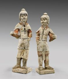 """PAIR TANG PAINTED POTTERY FIGURES. Pair of Chinese Tang Dynasty, painted pottery figures; superbly modeled guardian figures of two warriors; each in relaxed stance, dressed in well-appointed armor and helmets; showing fine detailing with some remaining gilt pigments; each on a plinth base; H: 22 1/2"""" (taller)"""