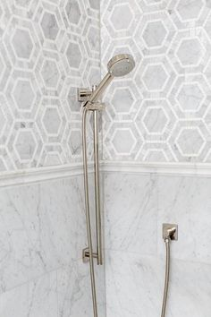 Gorgeous shower features marble hex tiles on upper walls and stacked marble tiles on lower walls ...