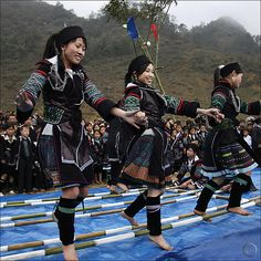 Black Hmong dancing over clapping Bamboo