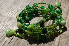 Lariat necklace with lots of different glass beads in nice bright shades of green. Lariat necklaces have no clasp and can be worn in many different ways.