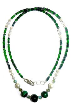 This classic necklace was handmade in Downtown Noblesville using beads from around the world. The green central stones are genuine Malachite from Congo. The green beads are seed beads which are common on Maasai patterning and design making. The white beads are pearls while the clear beads are glass crystals and metal spacer beads are included as well. Make this necklace yours today. It is both adjustable given the loops at the end. It also can be wrapped around the wrist and worn as a wrap…