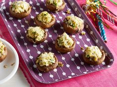 Artichoke-and-Cheese-Stuffed Mushrooms : Mushroom caps make perfect bite-size bowls for indulgent stuffings. Rachael Ray fills large white mushrooms with quartered artichoke hearts and Parmesan, then tops them with Asiago for a cheese overload.