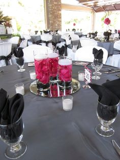 Centerpiece idea-I like the tall vases used to give the candles height and the mirror used to reflect candlelight at night. Touch of fuchsia in the candle setting as well to offset the black adn white in other candles and table decor.