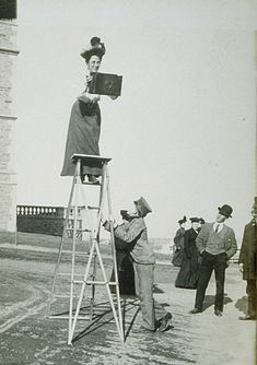 """Unknown photographer   Jessie Tarbox Beals working at the Louisiana Purchase Exposition   (The ladder is supported by her assistant, """"Pumpkin""""), 1904  Gelatin silver print  Radcliffe Institute, Schlesinger Library, PC60-18-22"""