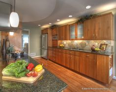 Cherry kitchen cabinets, wood floors, granite countertops, natural slate backsplash.