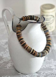 Vintage buttons, strung around a plump pitcher. #reuse, repurpose, #enamelware