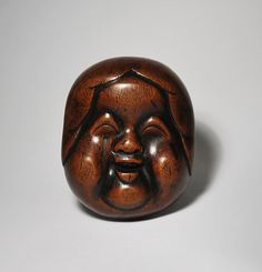 A marvelous boxwood folk art 'mingei' netsuke of a cheerful Okamé on one side and the reverse depicting Hyotoku, the stirrer of the elixir of immortality, through whose nostrils the artist has cleverly placed the himotoshi.  This netsuke would represent a talisman for happiness and good health.  18th Century.