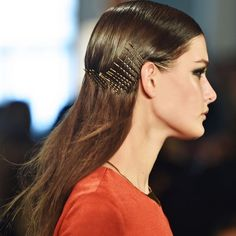 Create a deep side part and slick hair straight down with a shine pomade. Starting behind the ears, stick bobby pins in order all the way around to the opposite side