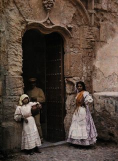 1924, Toledo, Spain --- Two girls wait at a church door in Toledo --- Image by © Gervais Courtellemont/National Geographic Society/Corbis
