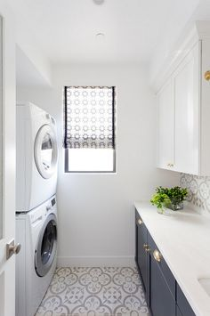 Two toned laundry room with navy lower cabinets and white upper cabinets. Flooring is a white and grey cement tile.
