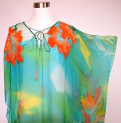 There are only 2  Kaftans available from this Range. These Kaftans are made from HAND PAINTED Silk Chiffon. They are absolutely Amazing !!!! This Kaftan is a longer length. This Kaftan is unlined. It can be worn as a dress or long top. It features a lace up front with dangle beading on the ends of the ties. It has magnificent Hand Beading on  the front of the Kaftan. Concentrating on the area around the Flower. Really, these kaftans are a work of art !!
