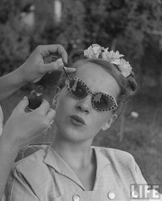 Teenage girl having nail polish touches added to her sunglasses, 1947.