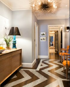 source: Thom Filicia  Chic, eclectic foyer with sea urchin pendant chandelier, coffee stained wood floors with painted silver chevron herringbone pattern, orange Louis chairs, mid-century modern credenza, turquoise blue lamp and gray walls paint color.
