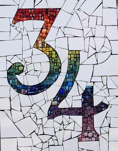 "Rainbow house number. Small glass ""mosaic"" tiles used for numbers in a background of ""smashed"" white porcelain tile. Scale contrast = piece size small in number, larger in ground. Dark grout toning with numbers."