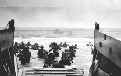 "D-Day: ""The men from my barge waded in the water. Waist-deep, with rifles ready to shoot, with the invasion obstacles and the smoking beach in the background gangplank to take my first real picture of the invasion."" -- Robert Capa"