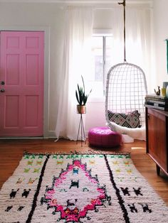 We're talking about bohemian decor and how it is the latest interior trend to hit Pinterest. Click thru to the post for more inspiration and design ideas on how to incorporate bohemian decor into your space. This azilal rug has the best jewel tones, and the white hanging rattan chair is perfect.