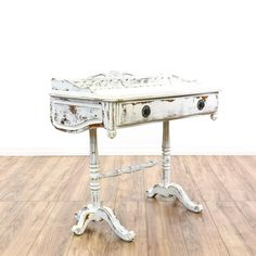 This shabby chic console table is featured in a solid wood with a distressed white paint finish. This small writing desk has intricate carved accents, 1 drawer and a curved rail top. Eye catching desk perfect for a small office or entryway! #shabbychic #desks #writingdesk #sandiegovintage #vintagefurniture