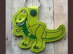 Rex the Dinosaur Key Fob  This design sews in the 4x4 hoop on green vinyl.   Available Formats Include - PES, PEC, HUS, JEF, VIP, VP3, and EXP  You may make this design as many times as you like, and you may sell your finished key fobs, however, please do not modify, share or resell my original digital design.  Thanks so much and happy stitching!!