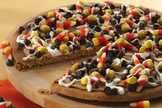 Halloween Pizza  1 roll (16.5 oz)  refrigerated sugar cookie dough  1/2 cup creamy peanut butter  1 cup candy corn  1/2 cup raisins  1/4 cup vanilla ready-to-spread frosting – NOT the whipped variety!!