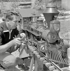 """September 1951. """"Walt Disney oiling parts of the locomotive of his scale model steam railroad, the Carolwood Pacific Railway, in the backyard of his house in Los Angeles."""" Medium-format nitrate negative by Earl Theisen for the Look magazine assignment """"Walt Disney's Giant Little Railroad."""""""