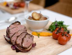 Roast Rump of Lamb served on a wooden board with rosemary potatoes and fresh vegetables. - By Lloyd Dobbie Rosemary Potatoes, Fulham, Wedding Menu, Fresh Vegetables, Spring Wedding, Lamb, Catering, Steak, Roast