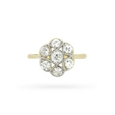 Seven old cut diamonds shape a lovely flower in millegrain-edged platinum atop this charming 1920s era diamond daisy cluster ring. A lacy openwork gallery, tapered shoulders, and a delicate shank in 18 carat yellow gold complete this delightful antique piece.